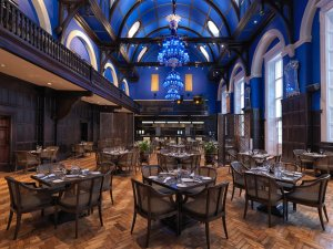 An image showing a great hall inside a dining hall with bright blue walls and flamboyant lighting fixtures