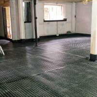 An image showing an interior with a rubber floor where work is being carried out to prevent damp