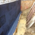 An image showing a construction area that has been damp proofed and will be a basement conversion once finished
