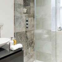 An image showing the interior of a bathroom with a contemporary design featuring tiles, a waterfall tap and a glass shower