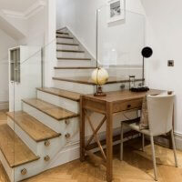 An image showing the interior of a property with wooden floors, white walls and a glass staircase