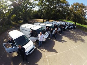 an image of a fleet of vans with their drivers
