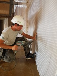 an image of a man drilling into a wall